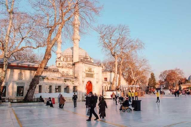 Open square dotted with people in front of the white facade of the Suleymaniye mosque domed structure with 2 minaretes standing either side