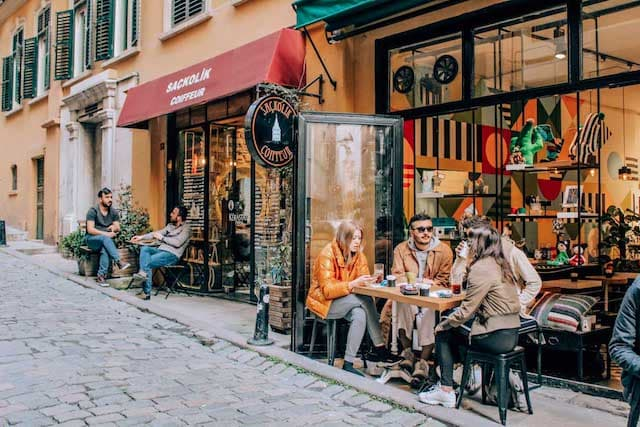 Cobbled street of the Karokoy neighbourhood featuring two restaurants with tables outside on the sidewalk with people eating and drinking