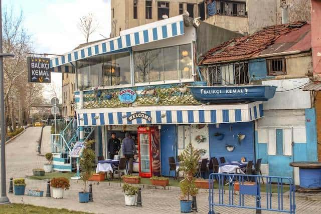 A fish restaurant near the Galata Bridge with a blue and white striped canopy above the first and second storeys