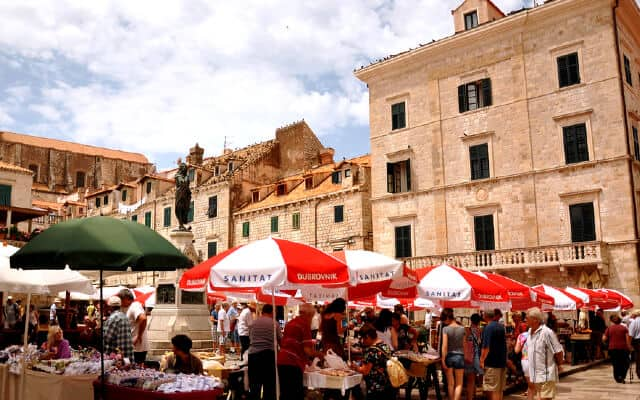 Red and white beach umberellas cover open air market stalls with stonewashing buildings in the background
