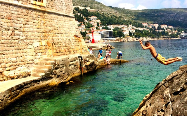 People swimming in the clear blue water outside the high walls of Dubrovniks Old Town