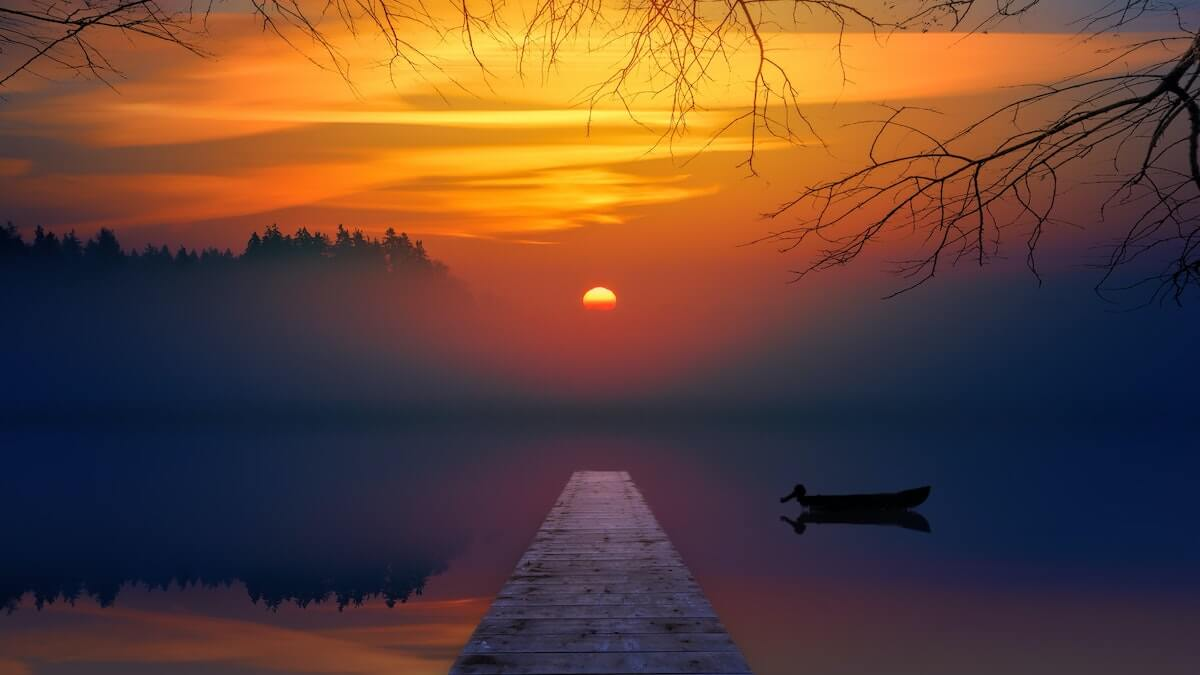 Best Sunset Quotes for Instagram Captions cover photo of a wooden pier over a lake at sunset