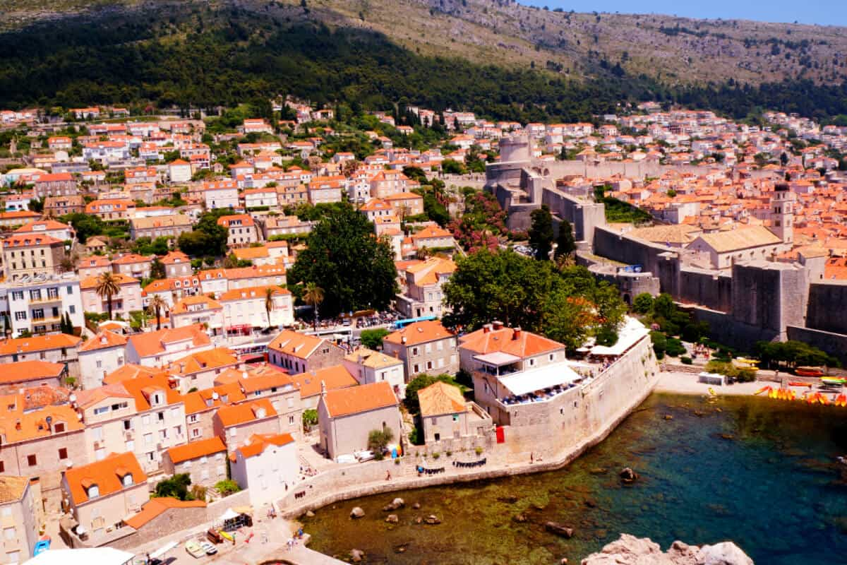 Aerial view of Dubrovnik old town with the harbour in the foreground and the terracotta rooftops of the city behind it as the hero image for the Best Things to do in Dubrovnik