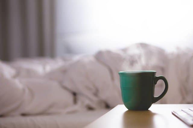 Green Coffee Mug on a wooden table next to a slept in bed