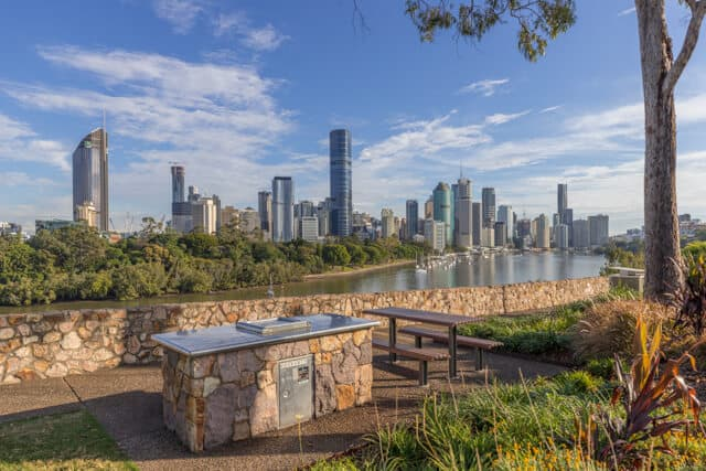 Outdoor BBQ area next to a picnic bench with Brisbanes skyline in the distance