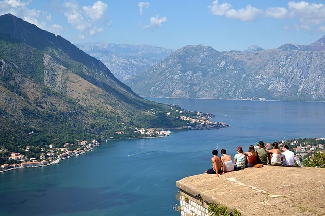People sitting with their backs to the camera looking out over Kotor Bay below