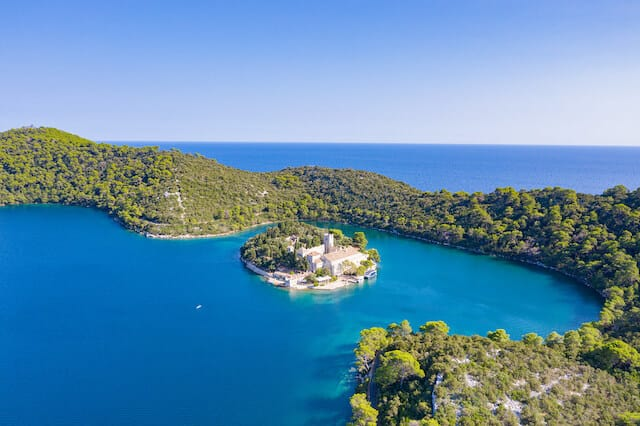 Aerial shot of lush green islands surrounded by turquoise blue waters of Mljet National Park in Croatia