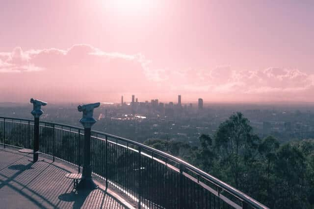Mount Coot Tha lookout with Brisbane city skyline in the distance under a pink sunset sky