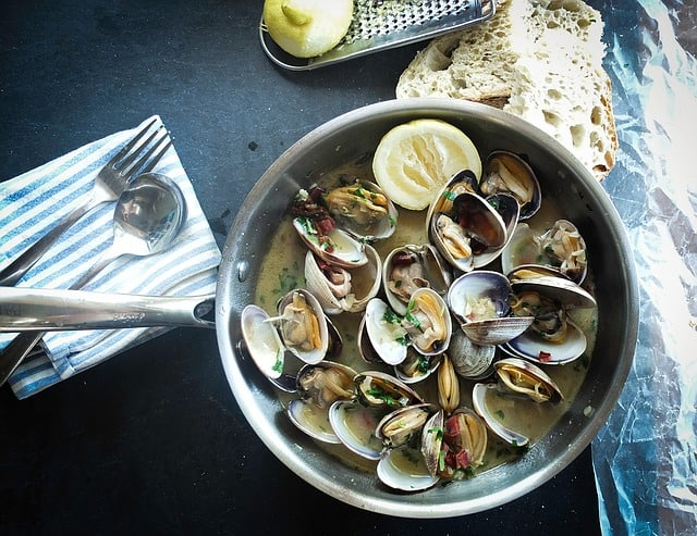 Muscles in a pan with a cream sauce and lemon wedge