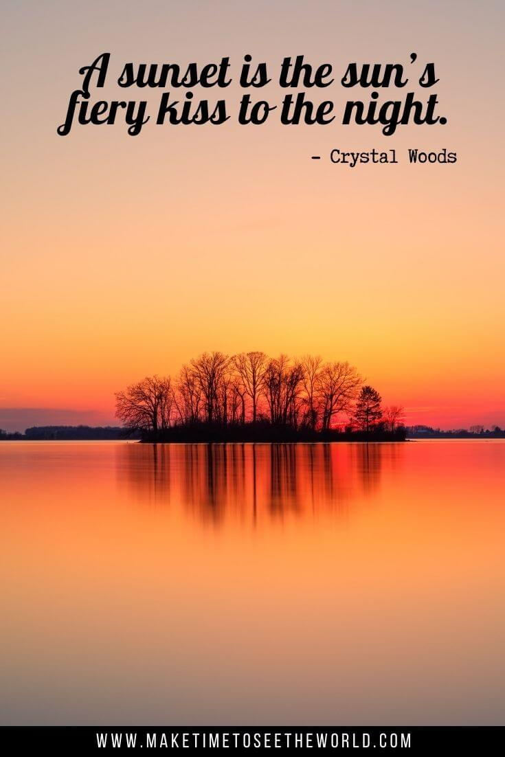 "A sunset is the sun's fiery kiss to the night."" - Crystal Woods text overlay above a lake with a small island in the middle under an orange sunset sky"