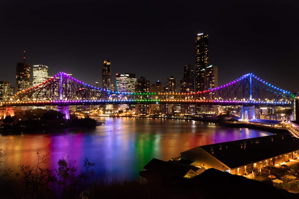 Things to do in Brisbane & Brisbane Travel Guide cover photo of the story bridge lit up in rainbow colors at night in front of the city skyline