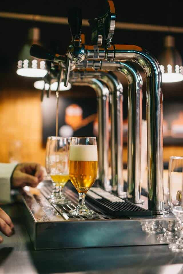 4 Shiny silver beer taps with two half pint glasses underneath the spouts, one glass full of beer, one being filled