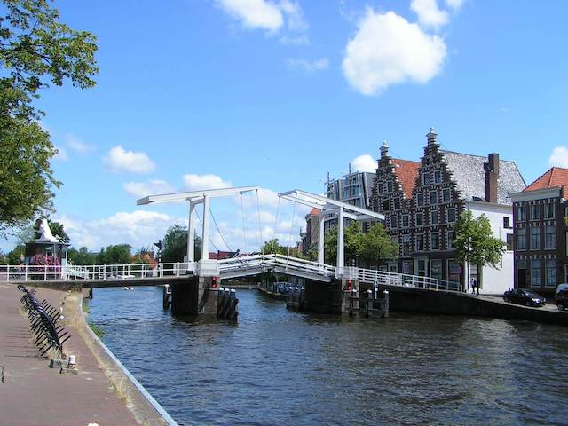 River with a white wooden bridge across and buildings on the far river bank