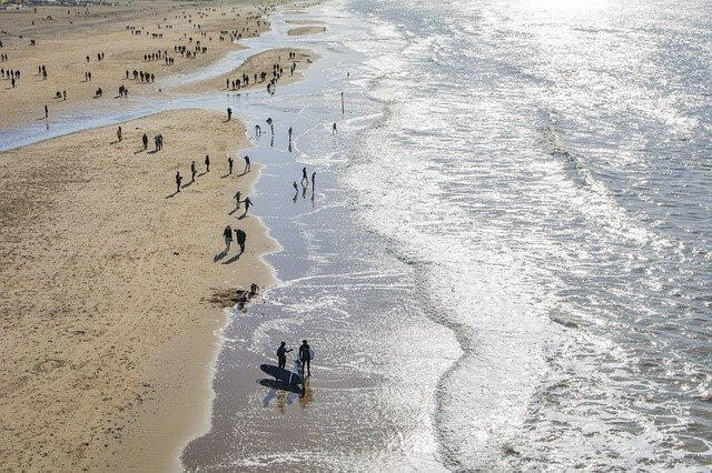 Aerial shot of a busy beach in Holland with people standing along the shoreline