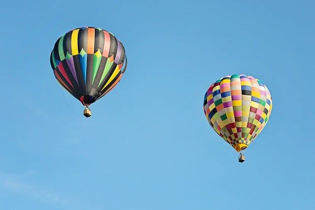 Two multicoloured hot air balooons flying high in the blue sky