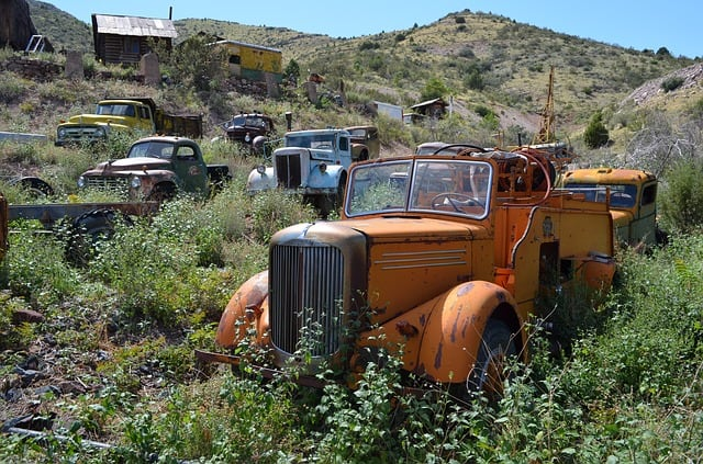 Rusted vintage cars in an overgrown field in Jerome Arizona