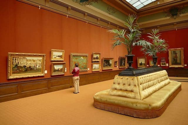 Inside Tylers Museum with white leather central seat, wooden walls with art work hung at eye level, a woman admiring the art wears a red sweatshirt