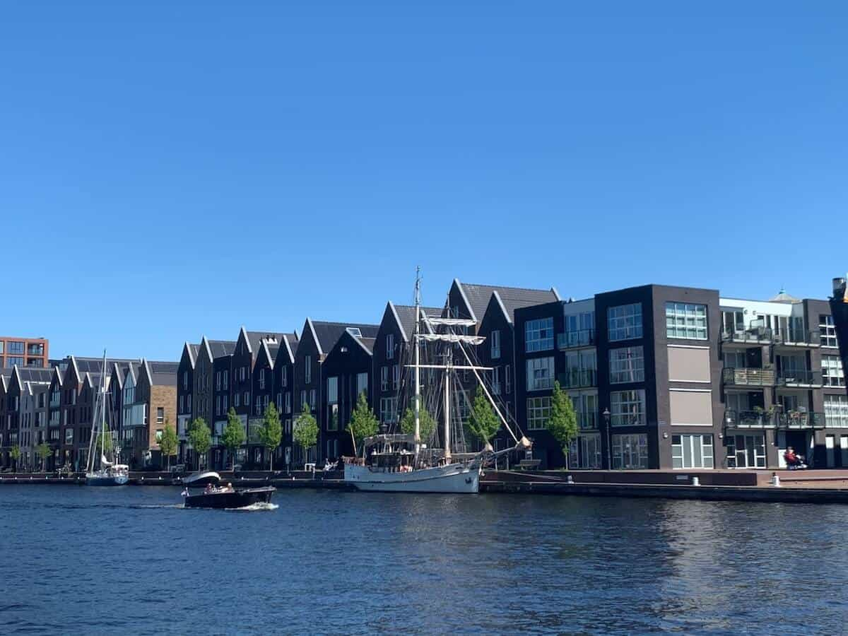 Buildings along the riverfront with a white tall ship docked to the bank - cover photo for the Top Things to do in Haarlem Netherlands