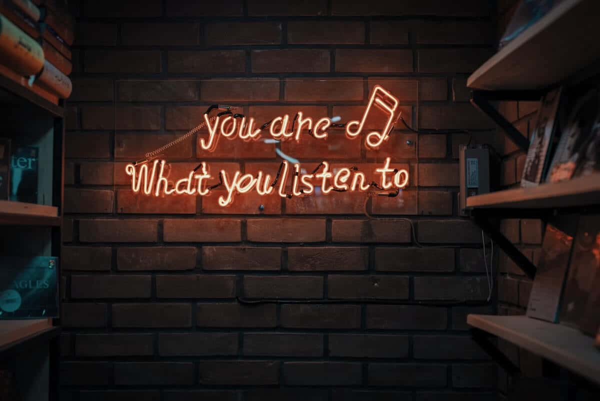 "Best Travel Songs cover photo of a pink neon sign against a brick wall that says ""you are what you listen to"""