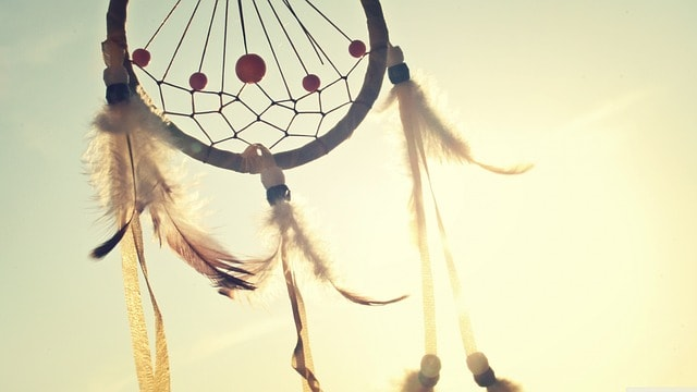 Dreamcatcher with feathers hanging from the loop in front of a sunburst