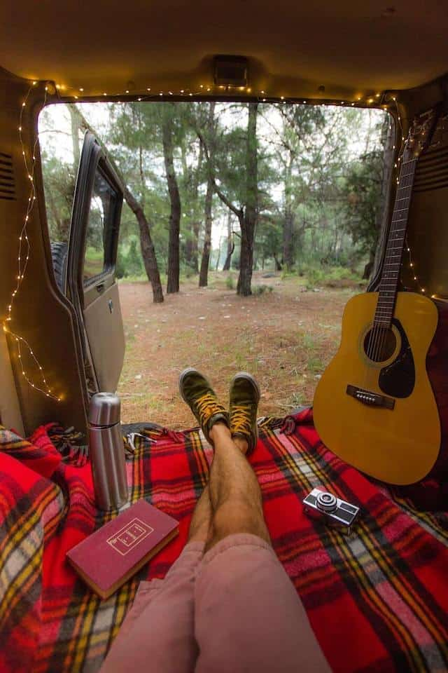 Campervan with the back doors open looking out into the forest. Mans legs wearing pink shorts pointed towards the open doors with a guitar sitting against the side of the vehicle on the right and the door framed by fairy lights