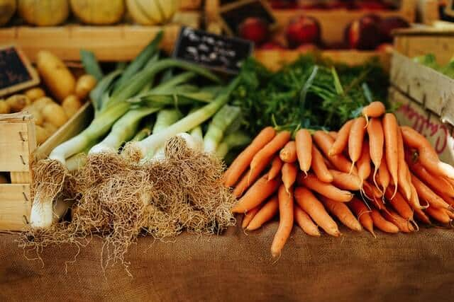 Fresh vegetables (wooden box of patoatoes next to loose leeks and carrots) lying on a wooden table at a farmers market