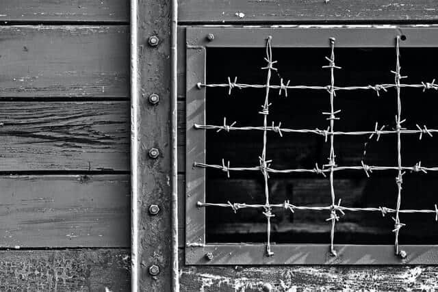 Black and white photo of a window covered in barbed wire bars at the Holocaust Museum El Paso