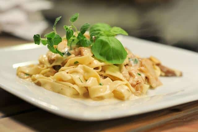 White plate containing wide ribbons of pasta in a white suace with mushrooms topped with a sprig of green leafy basil