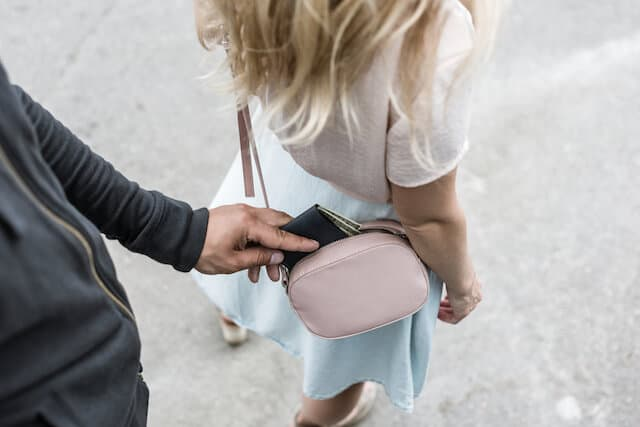 Mans hand taking a purse from a womans pink bag worn across her body and behind her back. She has blonde hair, a white shirt and a light blue skirt