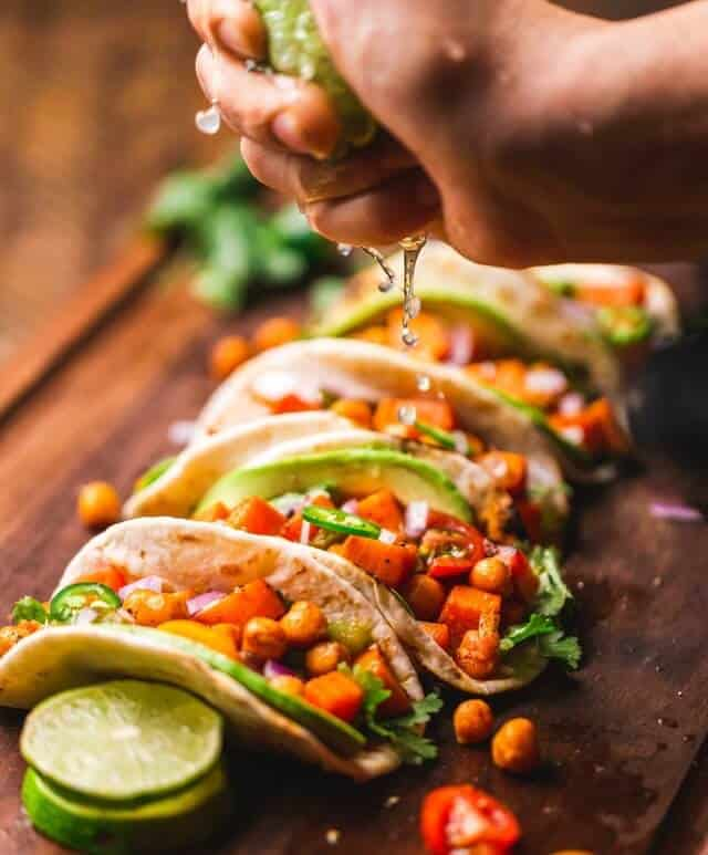5 Tacos on a wooden board lined up side by side, an hand hovering above them squeezing lime on to them
