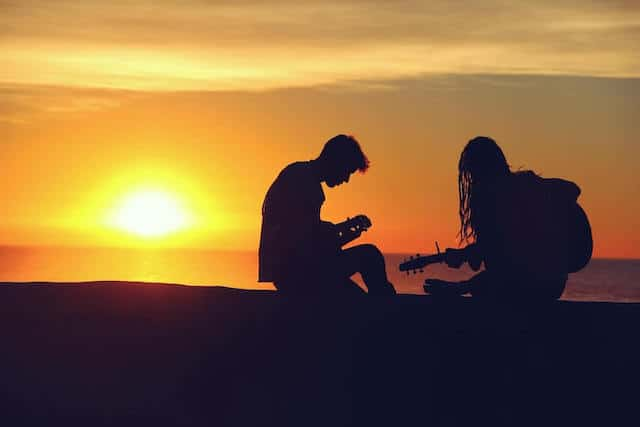 Silhouette on a Couple on the beach with the sun setting behind them. The woman on the right is holding a guitar, the man is sat looking at something in his hands