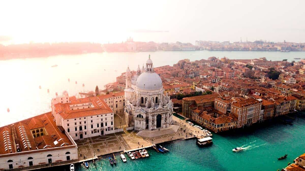 Aerial photo of Venice featuring an narrow strip of land packed with terracotta roofed buildings and a large while cathedral withwater either side for the header photo of Travel Tips for Italy to Know Before You Go