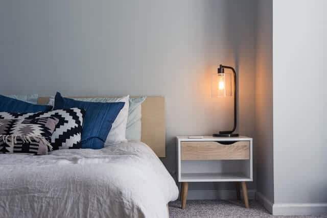 Half of a bed in a hotel room with white bedding and a navy blue accent pillow next to a wooden bedside table with a black filament bump lamp lit up on it