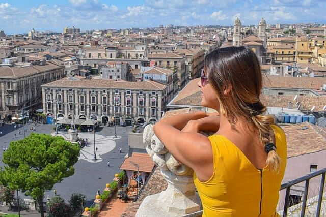 woman in a yellow sleevless dress with brown hair tied in a ponytail lookout our over the city of Catania in Sicily