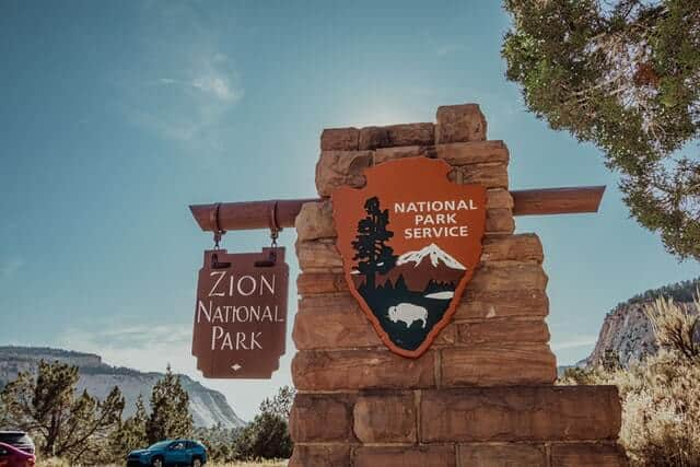 US National Park Service sign on a red brick wall with a hanging wooden sign saying Zion National Park