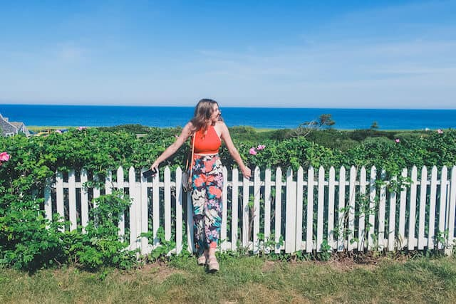 A woman leaning against a white picket fence with the ocean in the backgorund on Sconset Bluff Walk