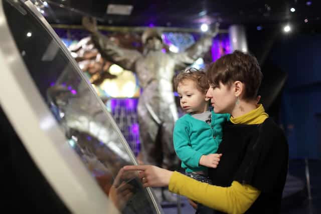 Woman holding a small child while touching an exhibit