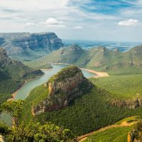 Best Time to Visit South Africa cover photo of a river running through the Green covered South Africa Mountain range
