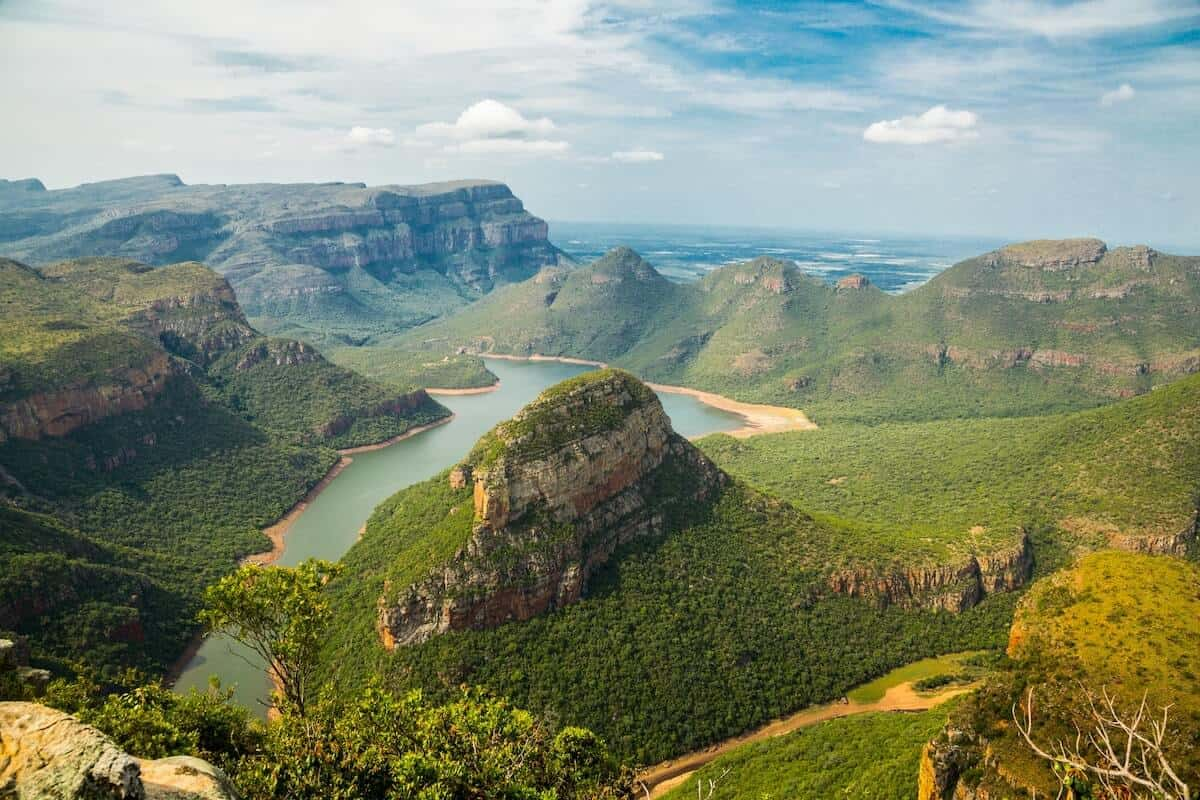 Best Time to Visit South Africa cover photo of a river running through the Green covered Drakensburg Mountain range
