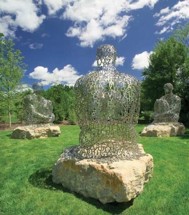 Frederik Meijer Gardens and Sculpture Park showing three metal statues of people sitting on rocks