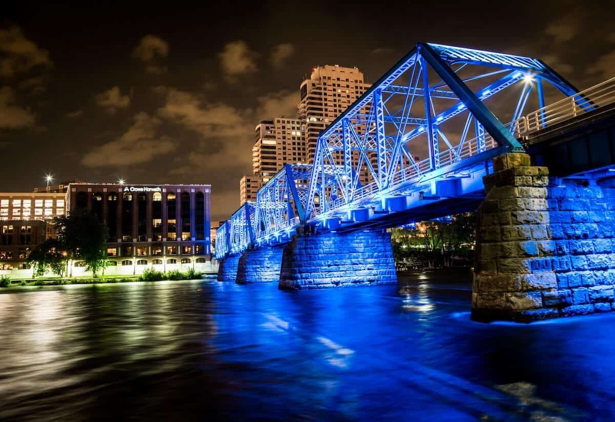 Fun things to do in Grand Rapids Michigan header photo of the blue bridge lit up in blue lights at night