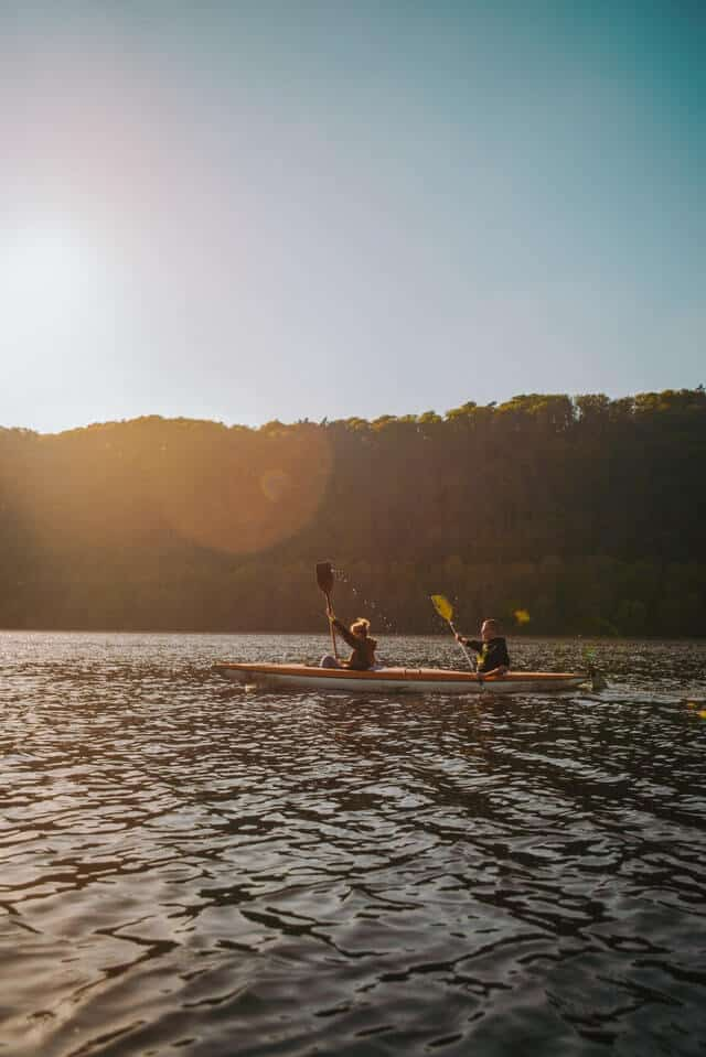 A double kayak being paddled by two people on Huron River