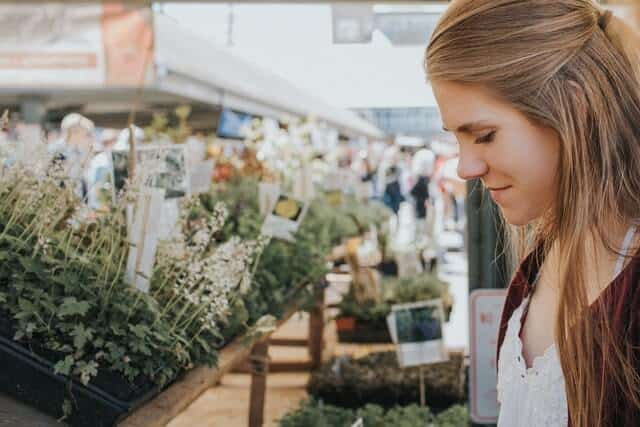 Woman looking at plants at a farmers market