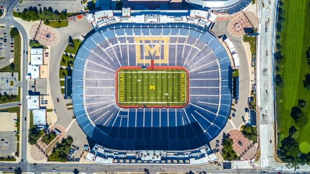 Top down shot of the Big House Stadium with green rectangylar playing field at the centre surrounded by thousands and thousands of blue seats