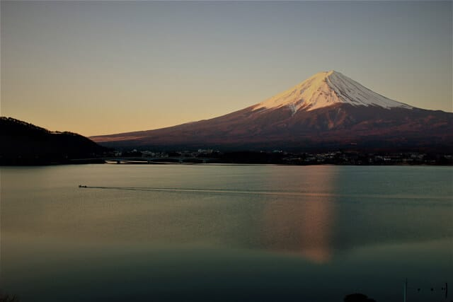 Still lake with a snow capped Mount Fuji in the background at sunrise