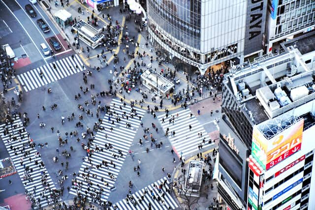 Aerial view of the manic Shibuya Crossing with three diferent zebra crossings going in different directions each covered with people and surrounded by skyscrapers