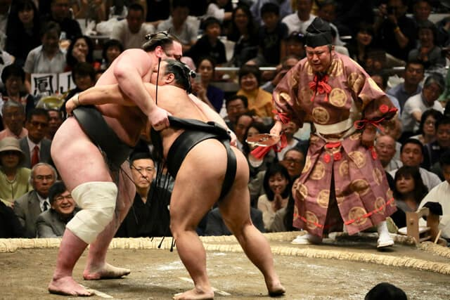 Two sumo wrestlers in the ring, a robed referee stands in the background and fans surround the ring