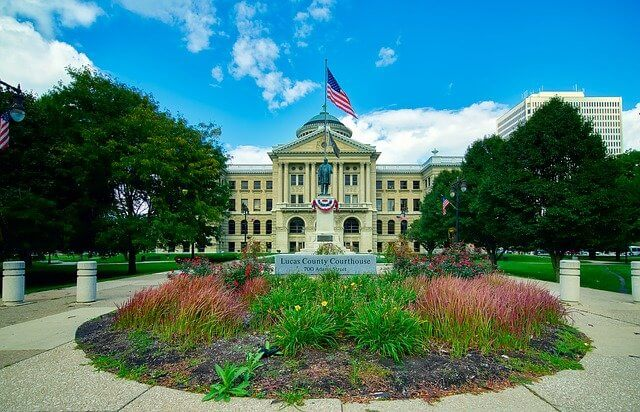 Large white town hall building with the American flag flying above and a sculpted garden in front