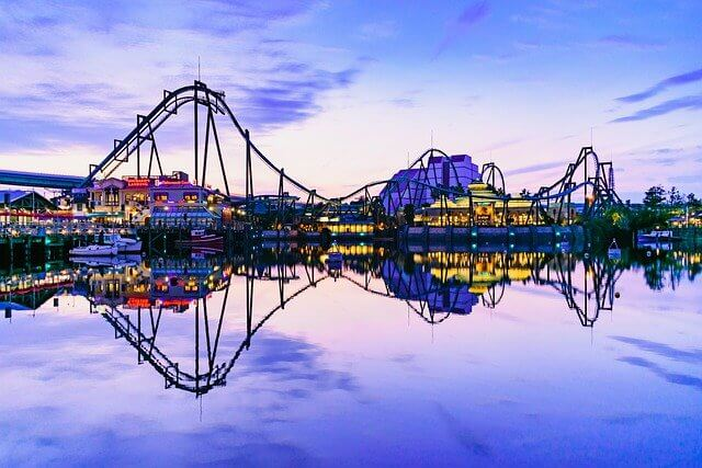 Unviseral Studios theme park at dusk, with rollercoasters rising in waves into the sky