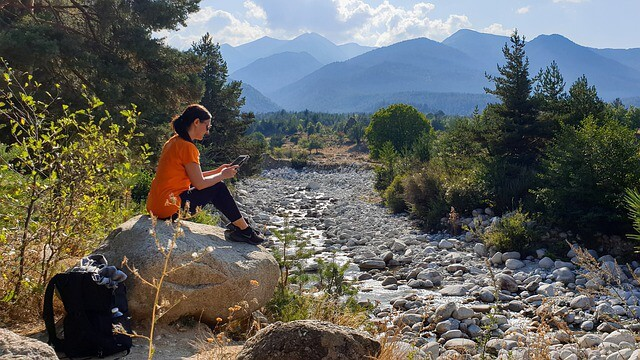 Woman on an ipad sitting on a boulder next to a river in Nature